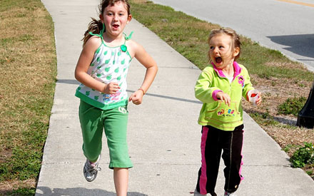 Two young girls running on sidewalk